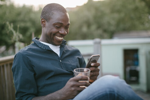 Smiling mid adult man using mobile phone while holding glass at porch - MASF10068