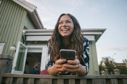 Happy mid adult woman using mobile phone while leaning on railing at porch - MASF10071
