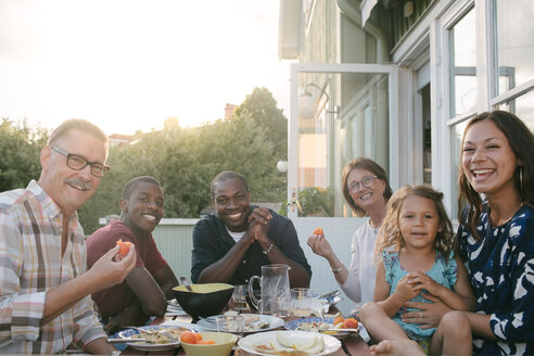 Portrait of smiling multi-generation family enjoying lunch at table on porch - MASF10077