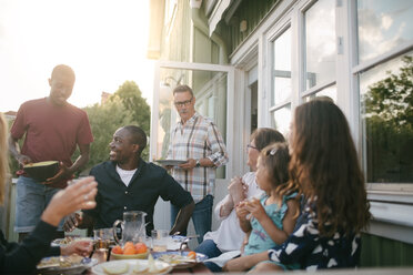 Happy multi-generation family enjoying lunch at porch - MASF10080