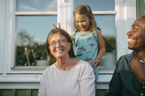 Happy multi-generation family against window at porch - MASF10083