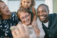 Cropped image of man showing mobile phone to happy family on porch - MASF10086