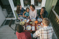 High angle view of multi-generation family having lunch at table on porch - MASF10089