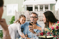 Mid adult woman showing mobile phone to family while sitting in backyard - MASF10101