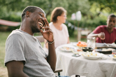 Mid adult man smiling while sitting by table during garden party - MASF10107