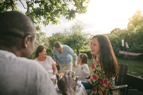 Mid adult woman smiling while having lunch at table during garden party - MASF10110
