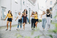 Full length of happy female friends having fun on cobbled street by buildings - MASF10113