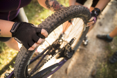 Low section of female friends holding bicycle wheel on dirt road - MASF10134