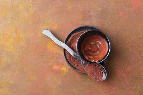 Red clay on spoon and plate and stirred in a bowl - MYF02059