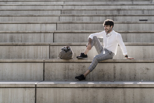 Young man with headphones sitting on stairs outdoors - GIOF04825