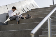 Smiling young man sitting on stairs outdoors using tablet - GIOF04837