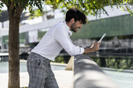 Smiling young man leaning on railing in the city using tablet - GIOF04840