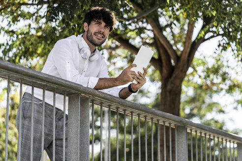Smiling young man leaning on railing in the city holding tablet - GIOF04843