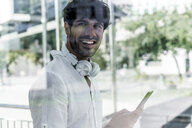 Portrait of smiling young man holding cell phone in the city - GIOF04846