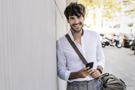Portrait of smiling young man with bag and cell phone in the city - GIOF04858