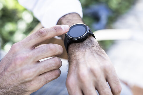 Close-up of man using smartwatch outdoors - GIOF04861