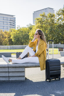 Smiling woman with suitcase sitting on a bench in the city - GIOF04870