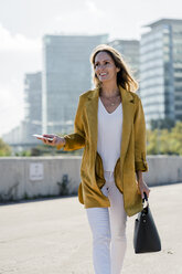 Smiling woman with cell phone and handbag in the city on the go - GIOF04879