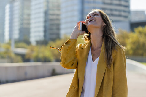 Laughing woman on cell phone in the city - GIOF04882