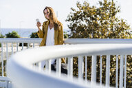 Smiling woman looking at cell phone on a bridge - GIOF04885
