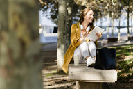 Smiling woman sitting on a bench in a park holding tablet - GIOF04891