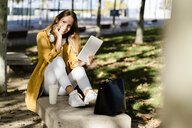 Smiling woman sitting on a bench in a park using tablet - GIOF04894