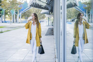 Woman with handbag and takeaway coffee walking along building - GIOF04897
