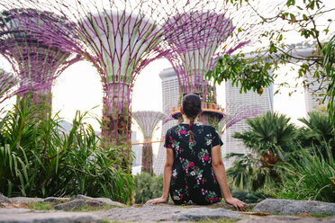 Singapore, Gardens by the Bay, woman sitting in Supertree Grove at sunset - GEM02639