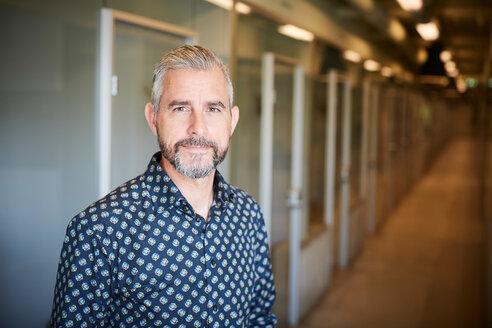 Portrait of confident mature businessman standing at corridor in creative office - MASF10169