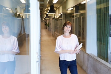 Portrait of confident businesswoman holding spiral notebook while standing at corridor in office - MASF10175