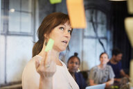 Businesswoman discussing ideas with colleagues over adhesive notes in board room - MASF10190