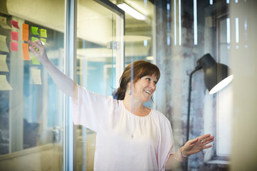 Smiling businesswoman discussing while pointing at sticky notes in creative office - MASF10193