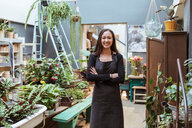 Portrait of smiling female owner standing with arms crossed by potted plants at store - MASF10238