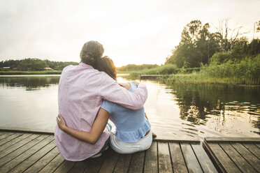 Rear view of couple sitting with arms around on jetty over lake during sunset - MASF10265