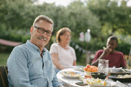 Portrait of senior man smiling while sitting against family at table during garden party - MASF10268