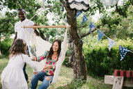 Father pushing hammock while happy woman holding hand of daughter in backyard - MASF10292