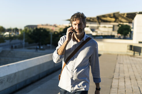 Mature man on cell phone in the city - GIOF04906