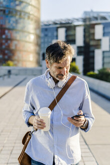Mature man with takeaway coffee and headphones using cell phone in the city - GIOF04912