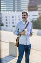 Portrait of smiling mature man with takeaway coffee, headphones and cell phone in the city - GIOF04915