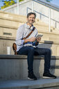 Portrait of smiling mature man sitting on steps with tablet - GIOF04921