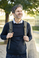 Portrait of smiling mature man wearing a backpack in the city - GIOF04936