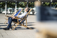 Mature man relaxing in deckchair on a square in the city - GIOF04948