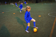Girl practicing soccer drill on field at night - HOXF04201
