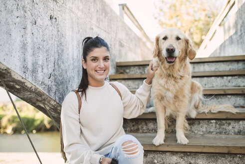 Portrait of a smiling young woman with her Golden retriever dog on stairs outdoors - RAEF02234