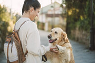 Happy young woman playing with her Golden retriever dog outdoors - RAEF02237