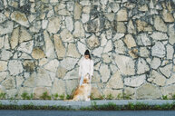 Young woman with her Golden retriever dog at a stone wall - RAEF02240