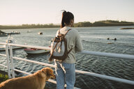 Woman looking at the sea with her dog - RAEF02243