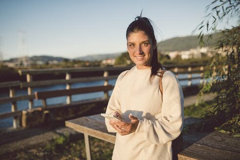 Portrait of smiling young woman with cell phone at the waterfront - RAEF02246