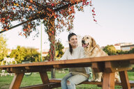 Smiling young woman with her Golden retriever dog resting in a park - RAEF02252