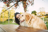 Portrait of young woman with her Golden retriever dog resting in a park - RAEF02255